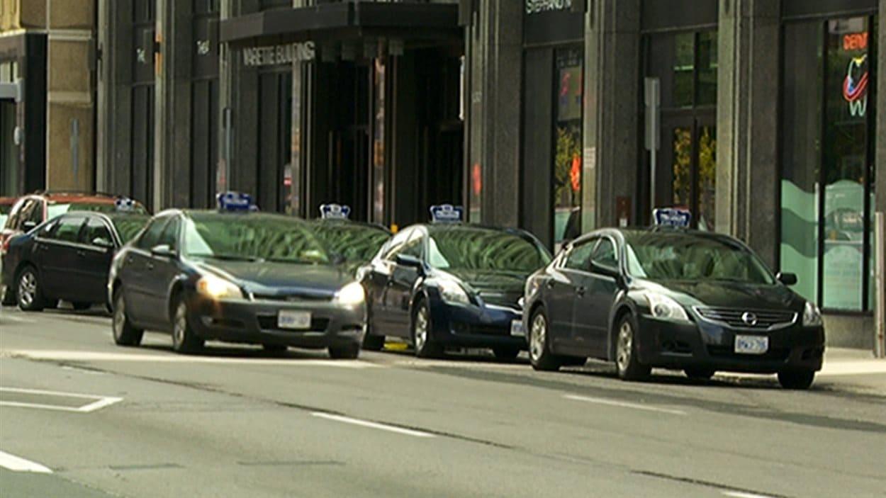 Des taxis sont stationnés et attendent des clients sur une rue d'Ottawa.