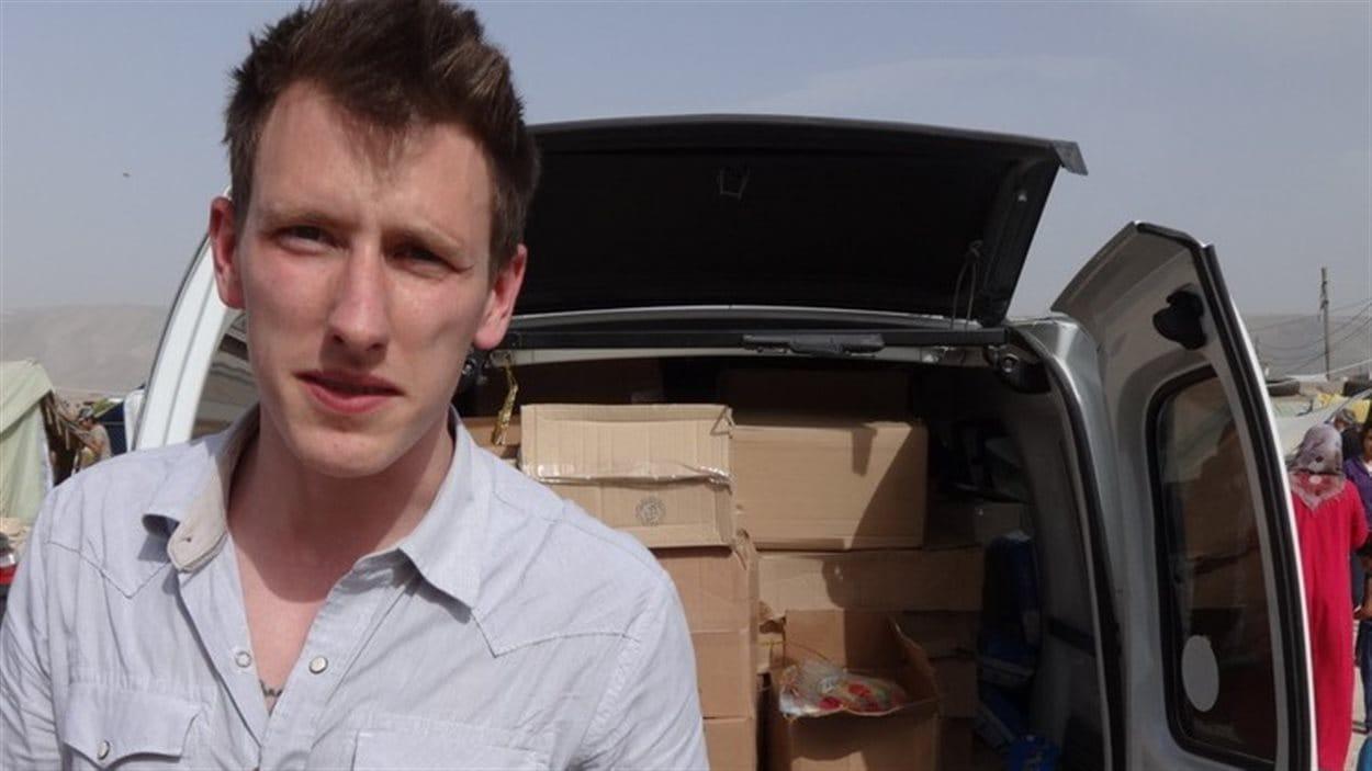 Une photo de Peter Kassig fournie par ses parents le montrant debout près d'un  véhicule  plein d'effets destinés aux réfugiés syriens.