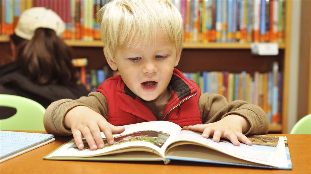 Jeune garçon lisant un livre à la bibliothèque.