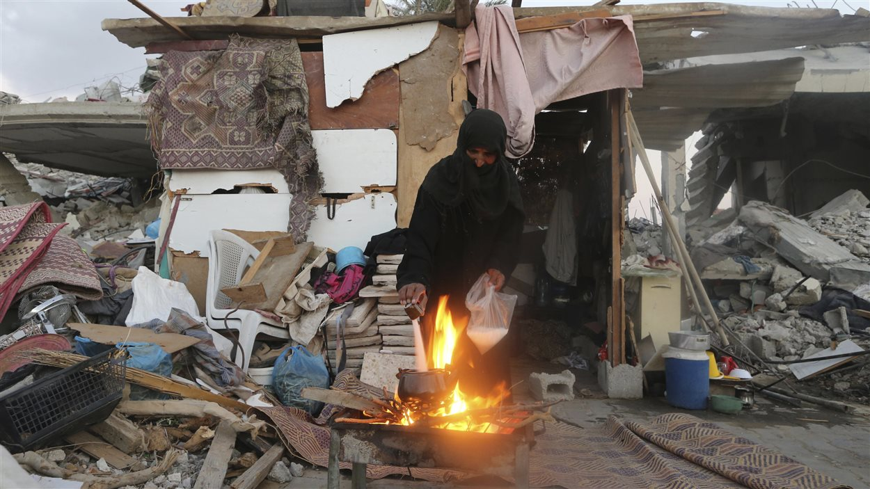 Une femme palestinienne prépare le thé à l'extérieur de sa résidence effondrée.