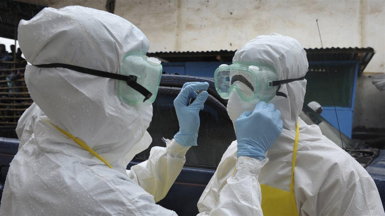Des travailleurs de la santé portent des vêtements de protection contre le virus Ebola à Monrovia, au Liberia.