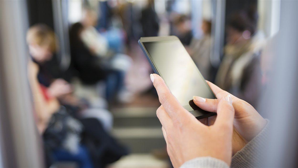 Une femme consulte son téléphone intelligent dans le métro