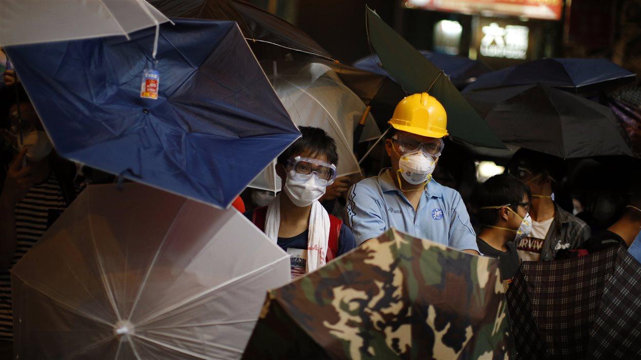 Des manifestants pro-démocrates utilisent des parapluies pour affronter la police