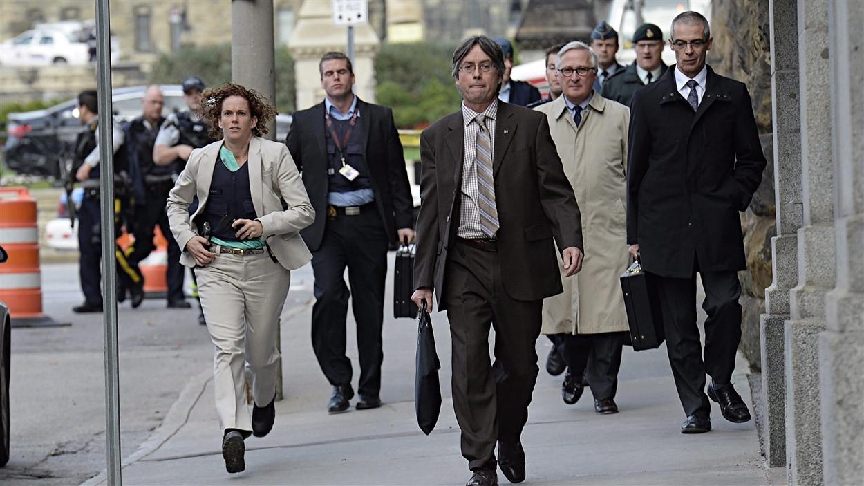 Des employés quittent le secteur après que des coups de feu eurent été tirés sur la colline du Parlement, à Ottawa.