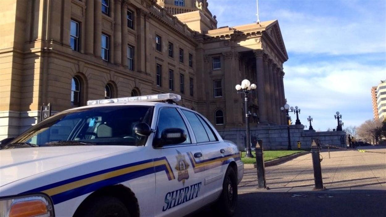 Une voiture de shérif est garée devant l'édifice de l'Assemblée législative de l'Alberta à Edmonton le 22 octobre 2014, à la suite de la fusillade survenue plus tôt à Ottawa.