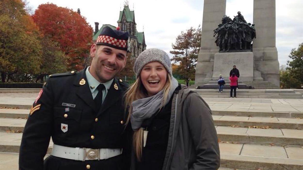 Une touriste pose aux côtés du caporal Cirillo au Monument commémoratif de guerre du Canada.