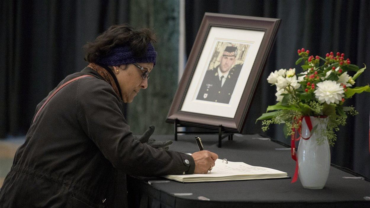 Une dame signe un registre de condoléances à l'hôtel de ville d'Ottawa.