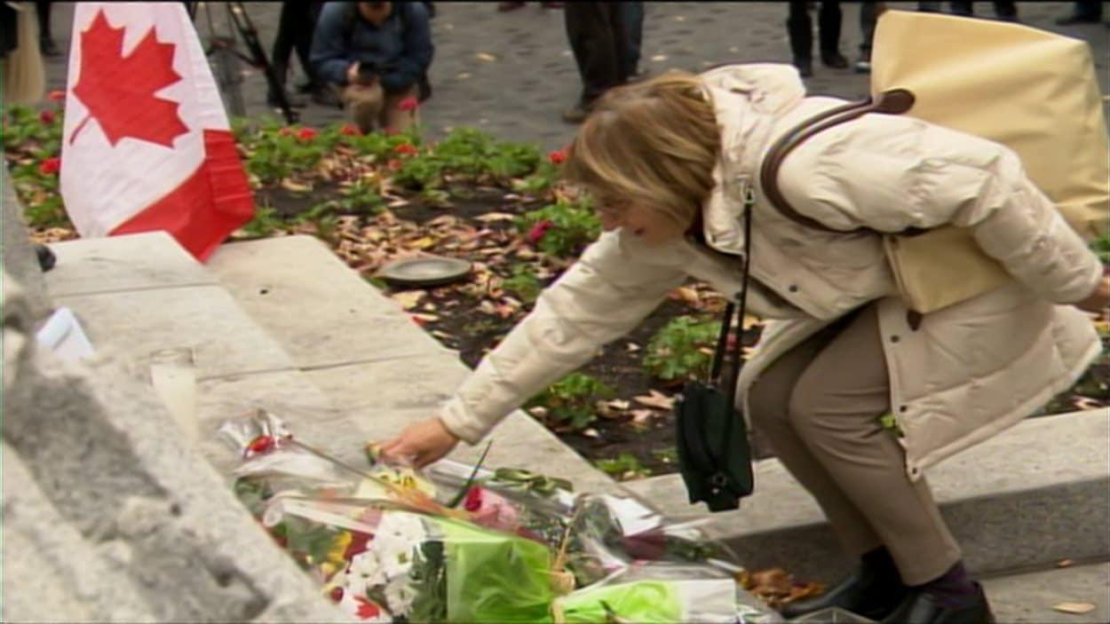 Une passante dépose des fleurs en hommage aux deux soldats tués cette semaine.