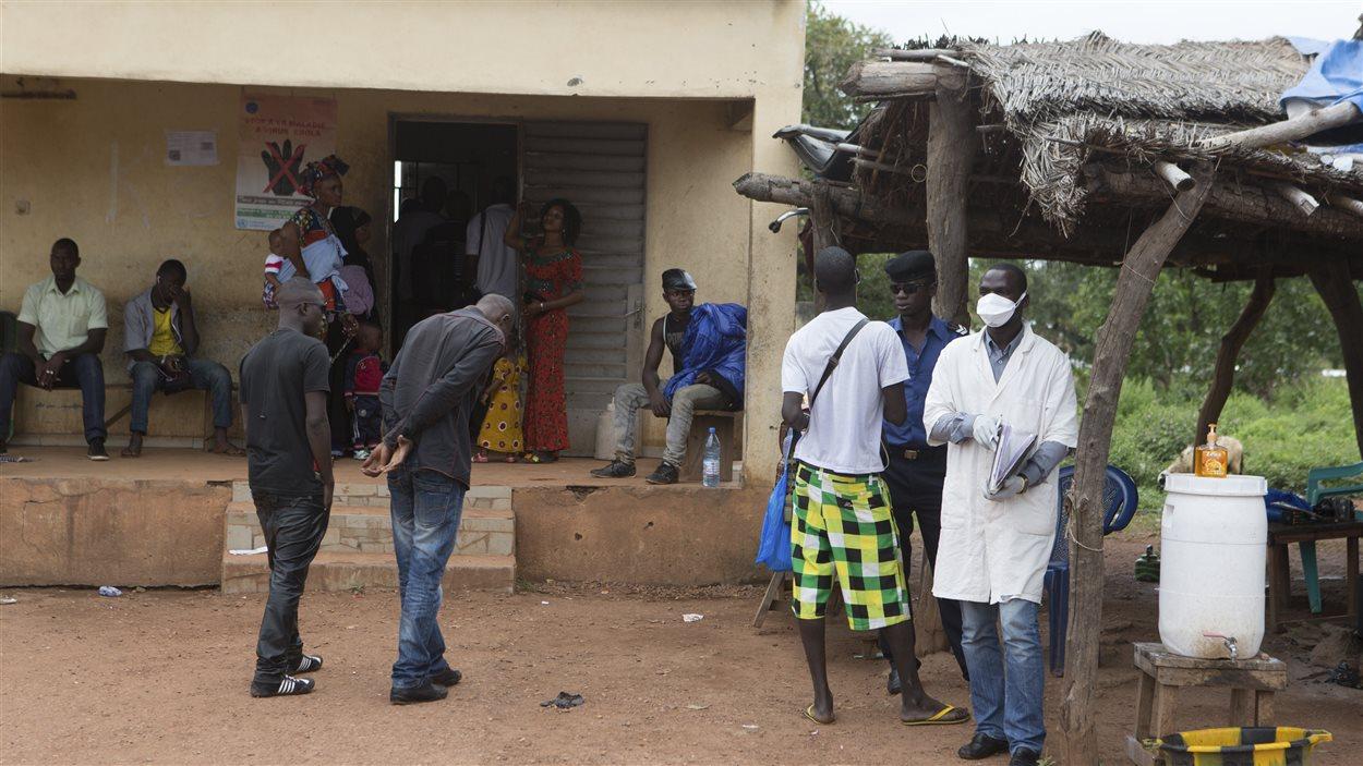À Kouremale, un travailleur de la santé attend pour prendre la température des gens qui passent la frontière de la Guinée vers le Mali.