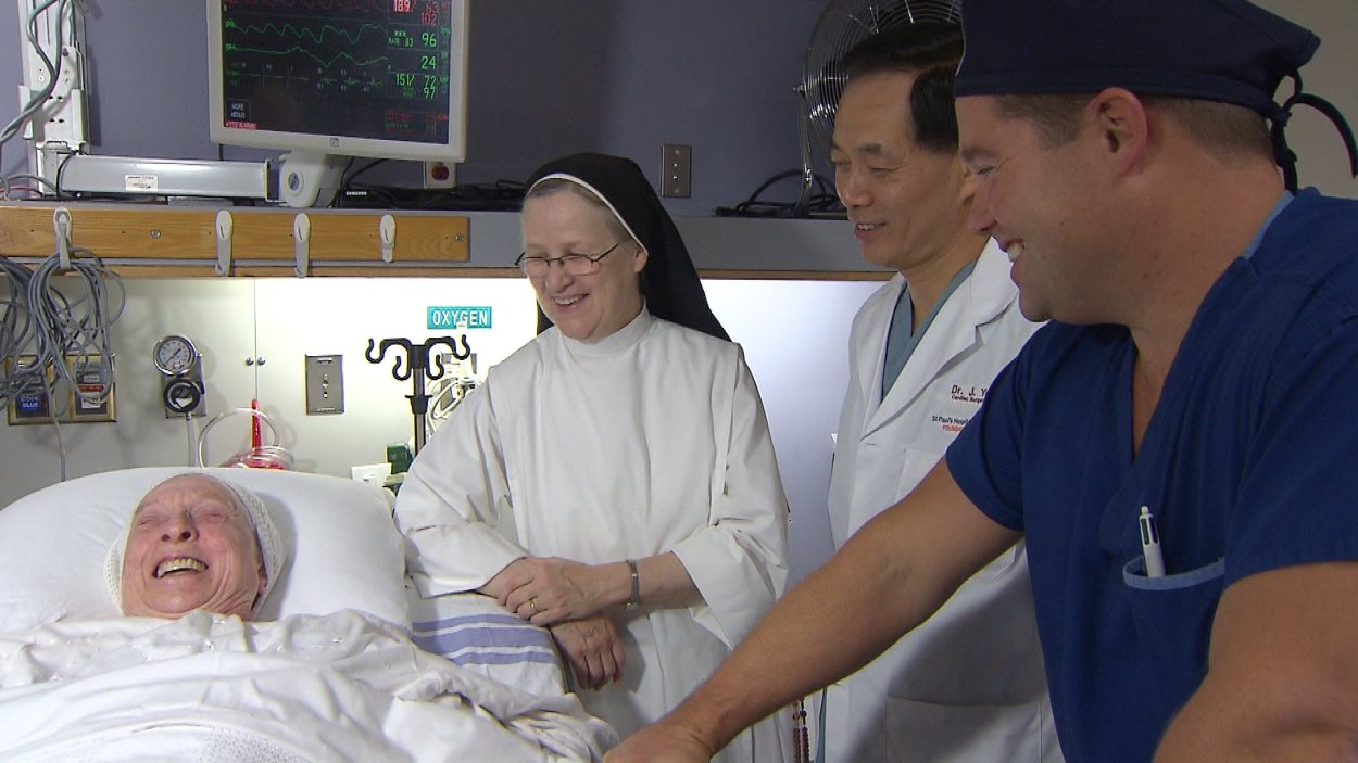 Soeur Theresa Stickley et le Dr David Wood (d) rencontrent les médias peu après une opération chirurgicale cardiaque que la patiente a subie sans anesthésie et qui a permis de remplacer sa valve aortique en une demi-heure.