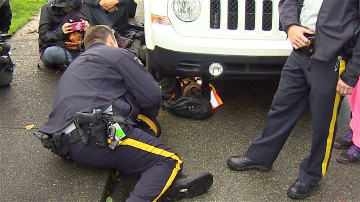 Un policier tente de convaincre un manifestant enchaîné à un véhicule de quitter les lieux.