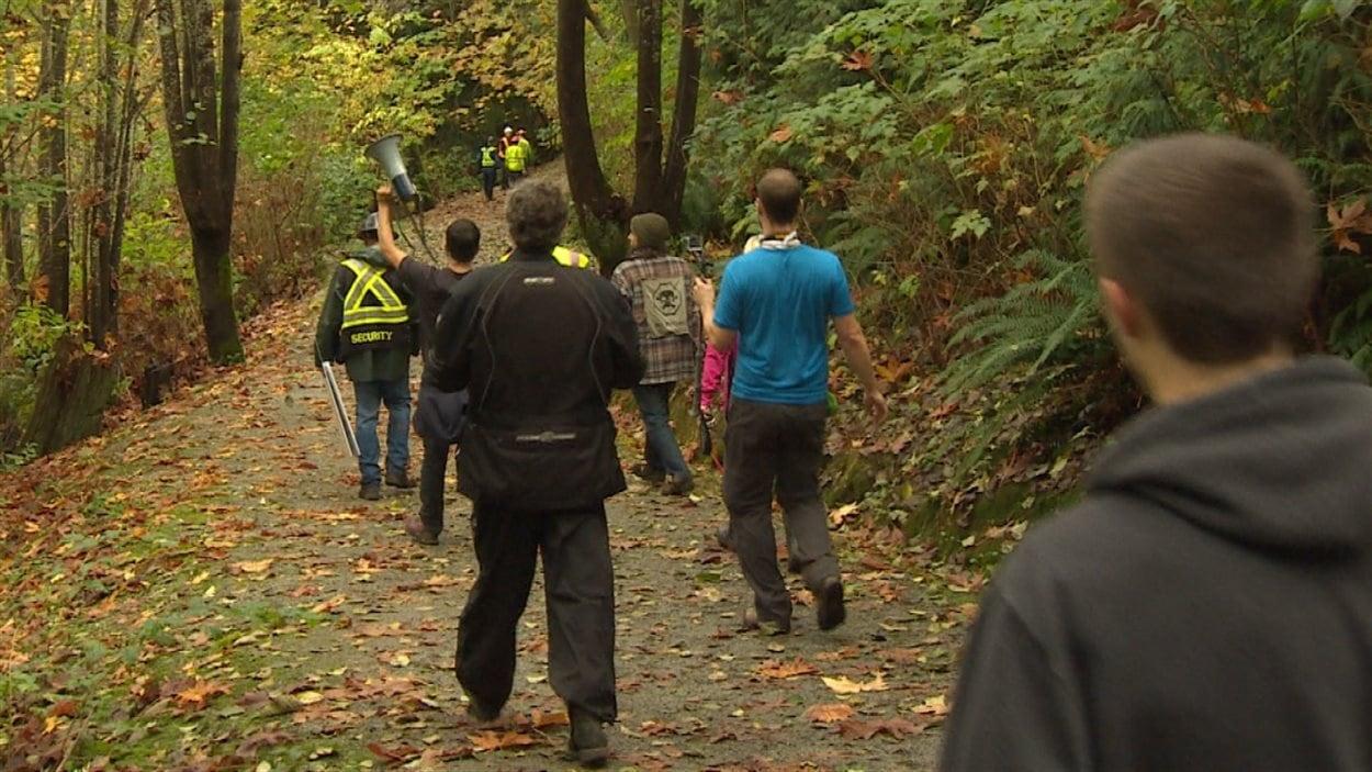 Des manifestants suivent des employés de Kinder Morgan qui tentent de faire des travaux d'arpentage sur le mont Burnaby.