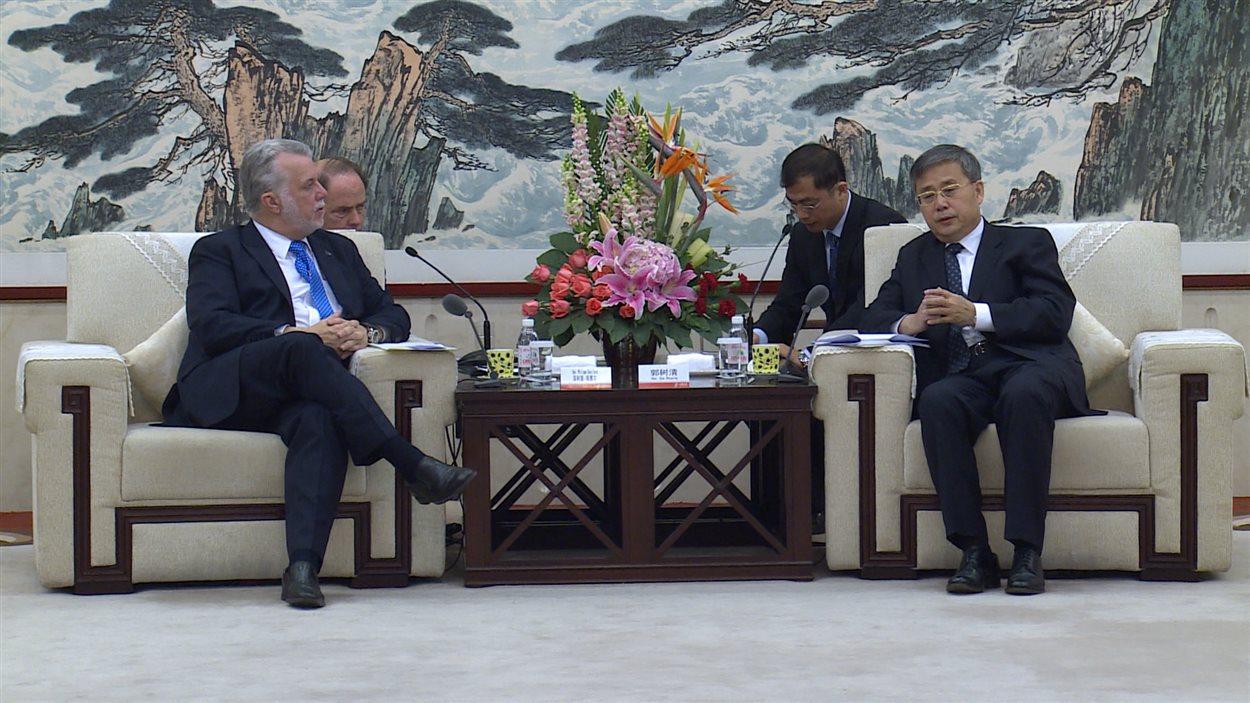 Le premier ministre du Québec, Philippe Couillard, serre la main du gouverneur du Shandong, Guo Shuqing, lors d'une rencontre à Jinan.
