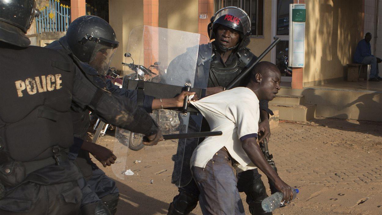 Des agents de police arrêtent un manifestant à Ouagadougou.