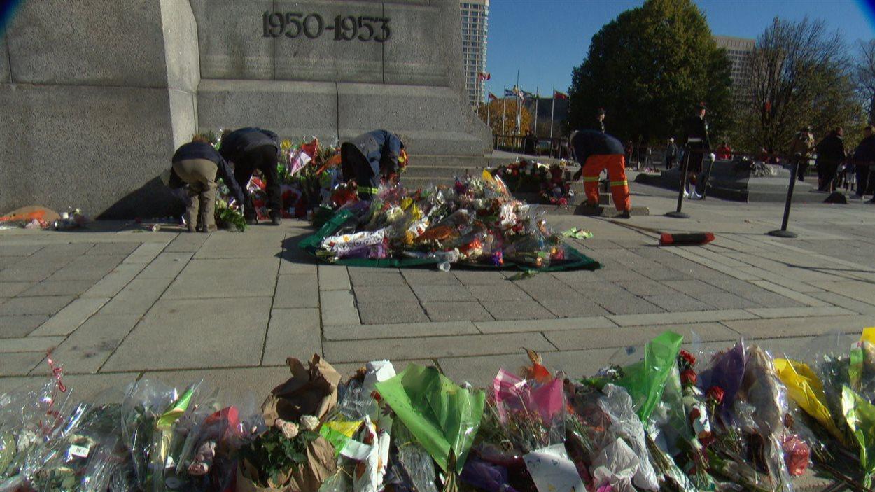 Des employés ramassent les fleurs et les cadeaux déposés au Monument commémoratif de guerre afin de préparer la cérémonie du jour du Souvenir.