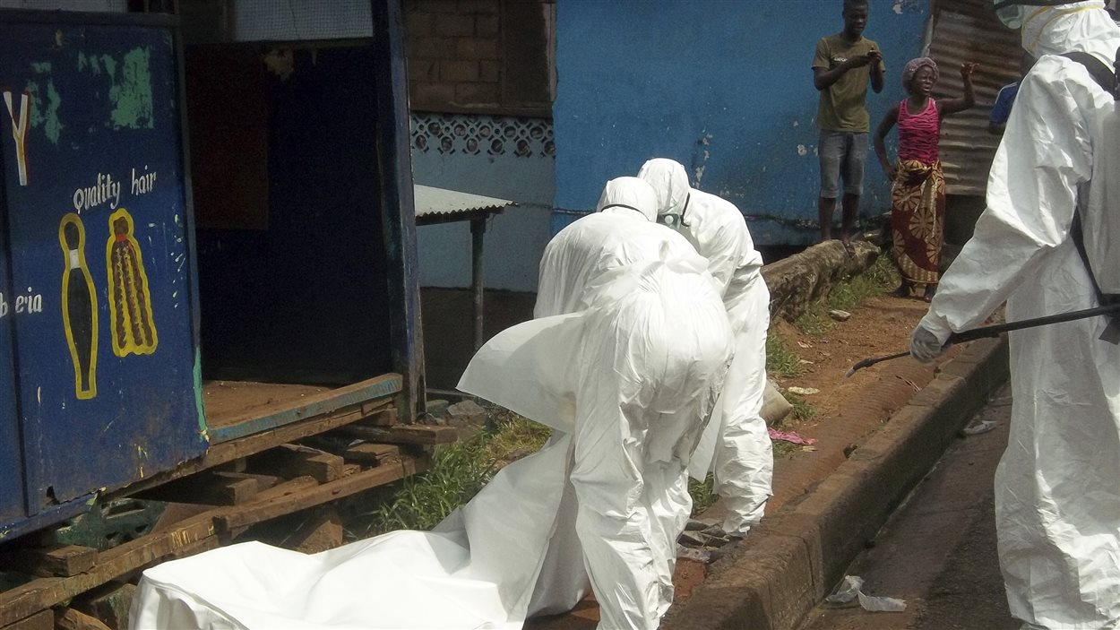 Des travailleurs de la santé emportent le corps d'une homme tué fort probablement par le virus Ebola