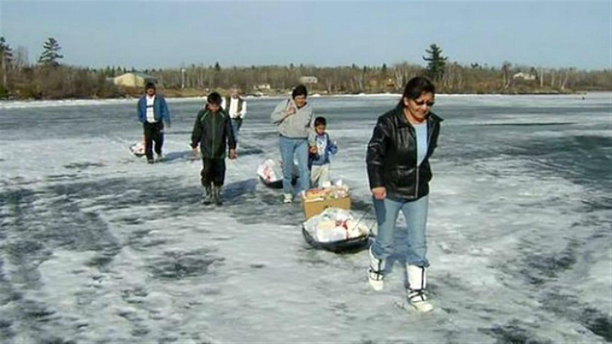Des membres de la Première Nation Shoal Lake 40 transportant leurs provisions