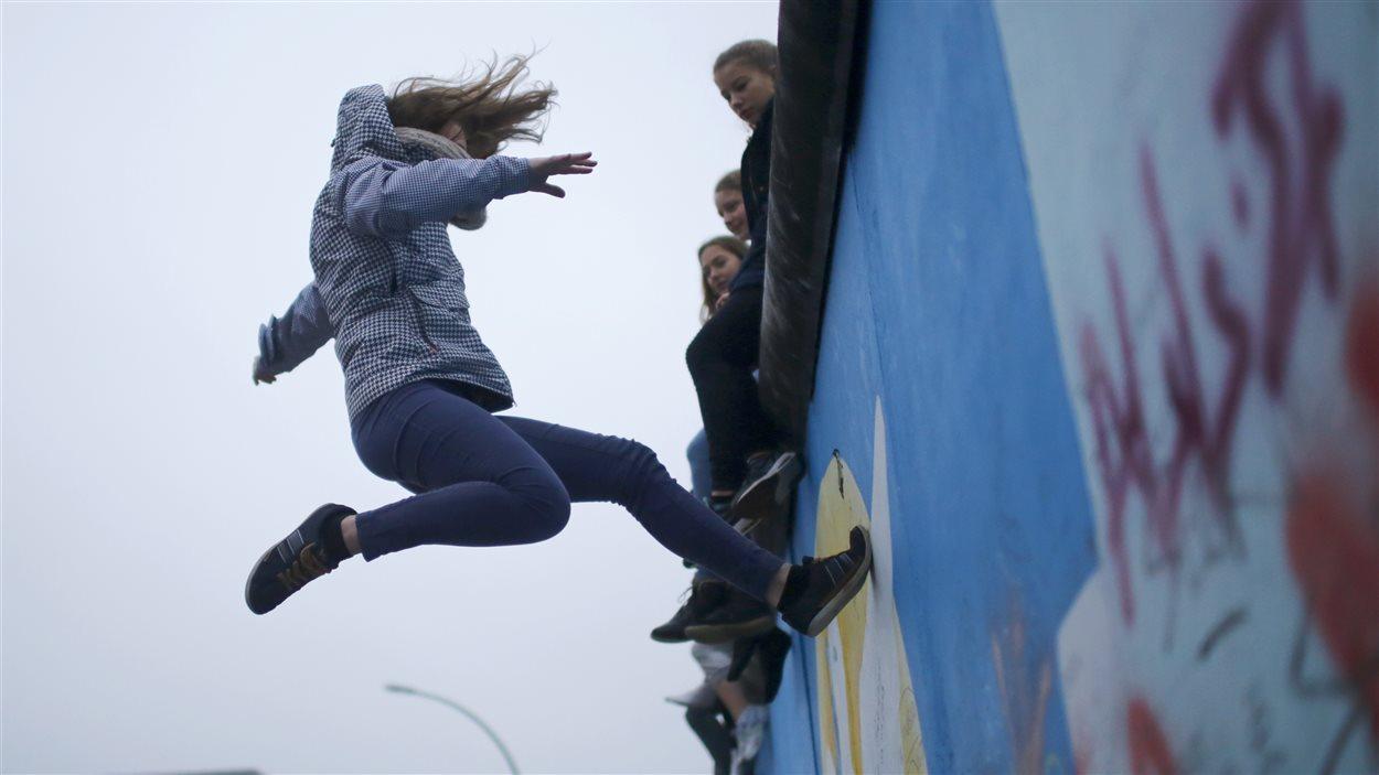 Une jeune membre du projet « Zirkus Ueberwindet Grenzen » (Cirque sans frontières) rebondit sur un trampoline sur l'East Side Gallery, la plus grande partie restante de l'ancien mur de Berlin.