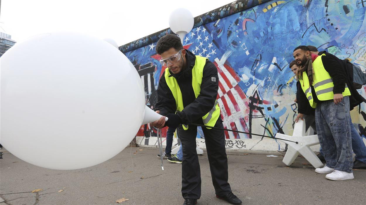 Un travailleur remplace l'hélium dans un des 8000 ballons lumineux placés sur l'ancien tracé du mur de Berlin, avant leur envol.