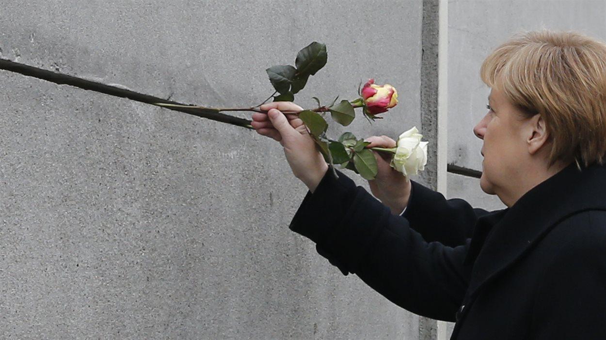 La chancelière Angela Merkel pique des roses dans le mémorial du mur de Berlin, en hommage aux Allemands de l'Est tués en essayant d'échapper au régime communiste.