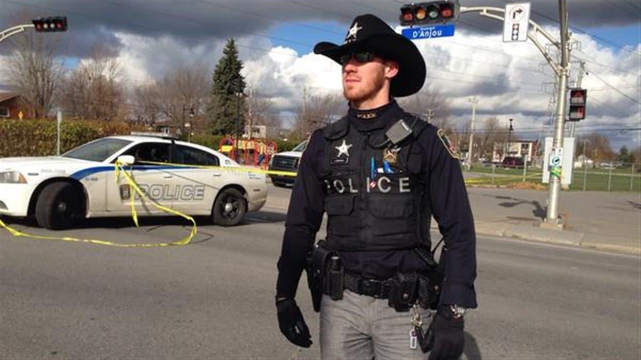 Un agent de la police de Châteauguay orborant le chapeau étoilé.