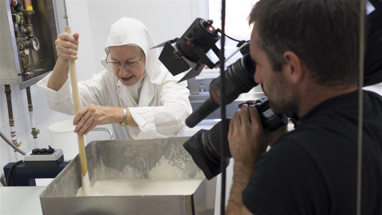 Soeur France mélange la pâte qui servira à fabriquer les hosties sous l'oeil attentif du caméraman