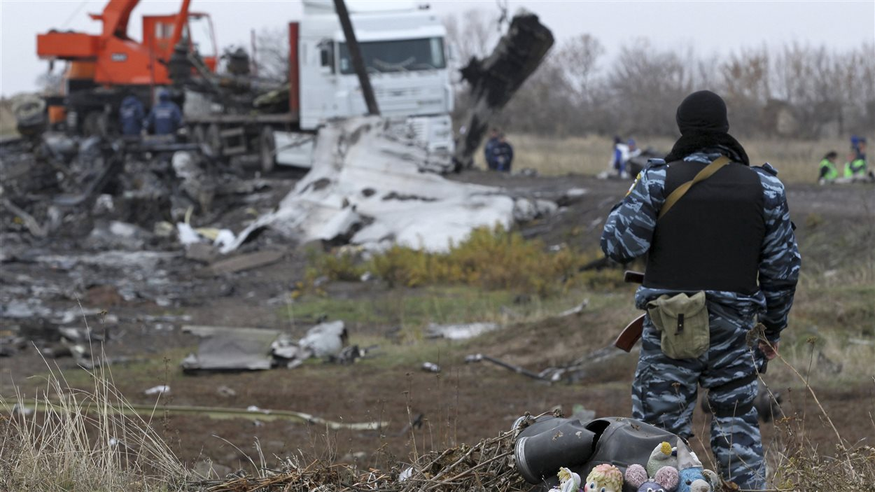 Un soldat pro-russes surveille les alentours du site de l'écrasement de l'avion de la Malaysia Airlines, qui s'est écrasé en juillet dernier, pendant que les débris de l'appareil sont rapatriés aux Pays-Bas.