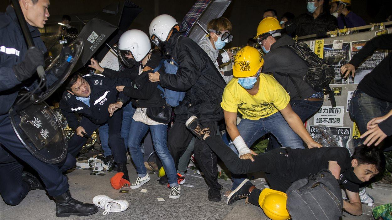 Des manifestants sont chassés par des policiers antiémeutes devant le parlement à Hong Kong, mercredi matin.