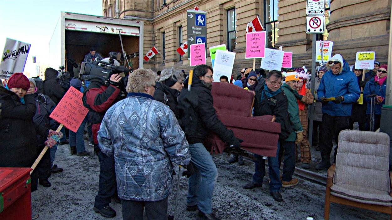 Des manifestants ont organisé un déménagement improvisé devant les bureaux de Stephen Harper, à Ottawa. (21-11-14)