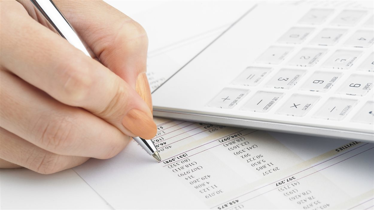 Une femme fait des calculs avant de remplir sa déclaration de revenus.
