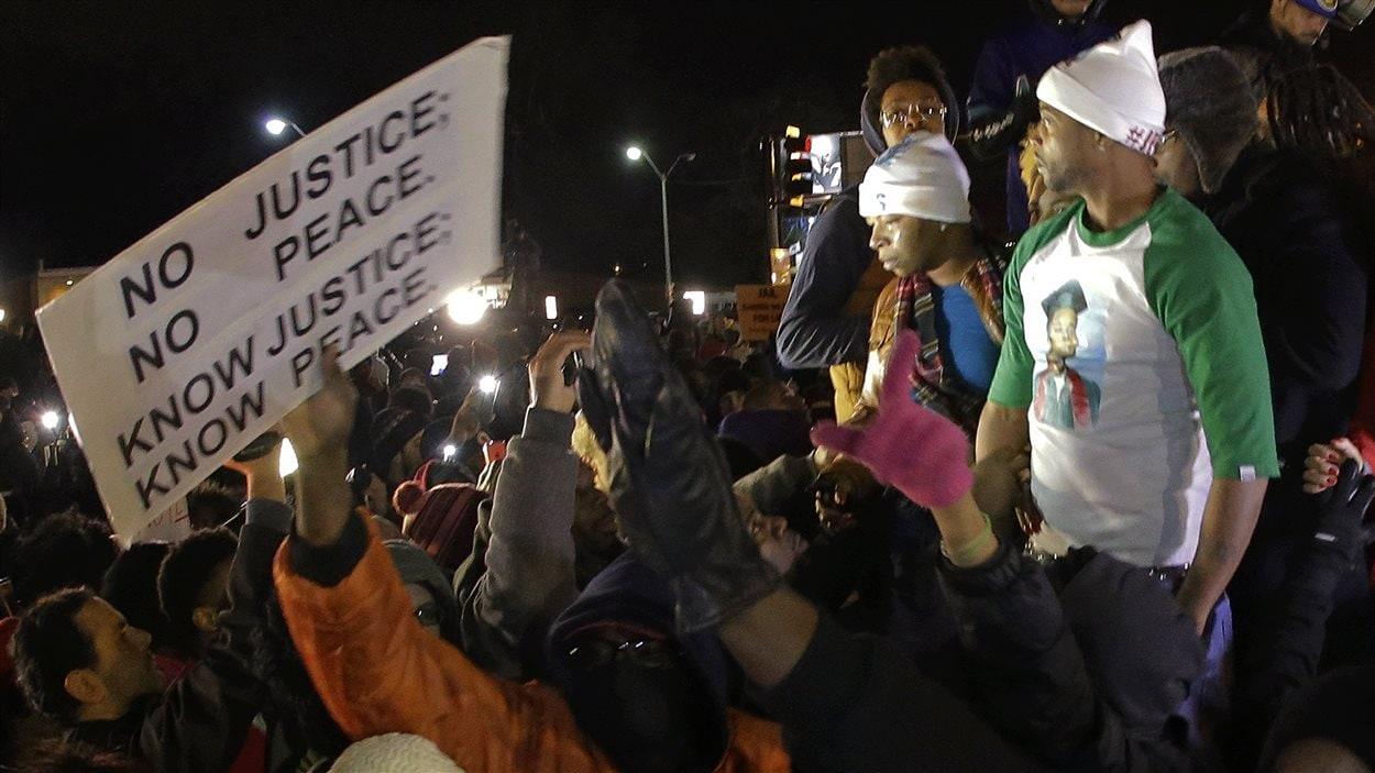La mère de Michael Brown, Lesley McSpadden (debout sur une voiture, à gauche) réagit à l'annonce du grand jury, lundi soir.