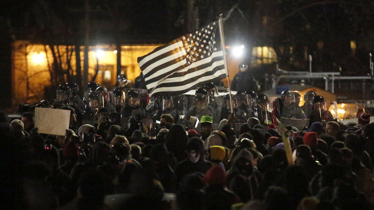 Des manifestants font face aux policiers devant le service de police de Ferguson, au Missouri, après que le grand jury eut annoncé sa décision de ne pas porter d'accusation contre Darren Wilson.