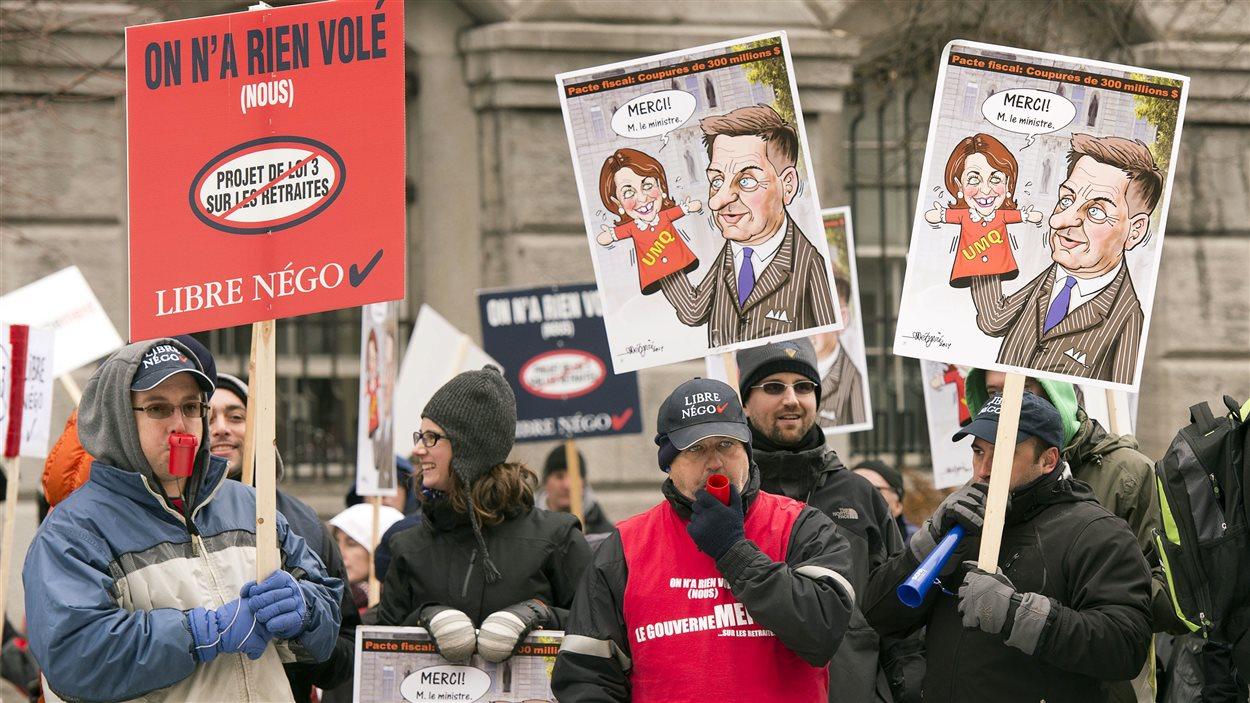 Des employés municipaux de Montréal manifestent devant l'hôtel de ville.
