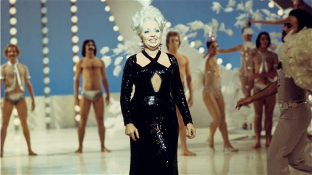Dans un studio de télévision en 1972, la chanteuse Muriel Millard entourée d'une troupe de danseurs.