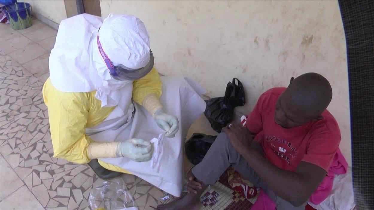 Un malade soigné par du personnel soignant en tenue médicale
