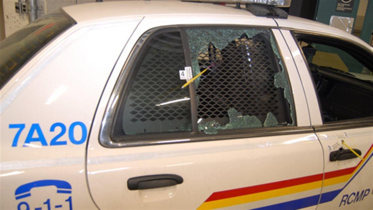 Une voiture de la GRC dont la vitre a été fracassée.