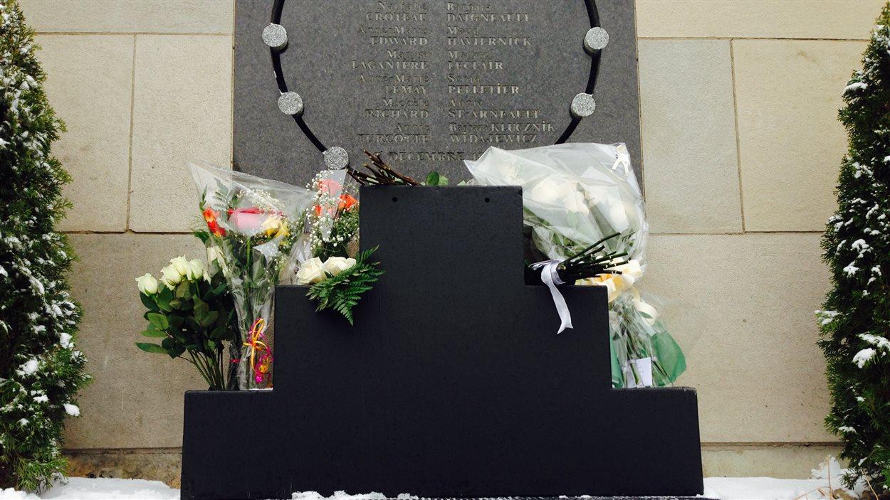 Des fleurs déposées devant la plaque commémorative