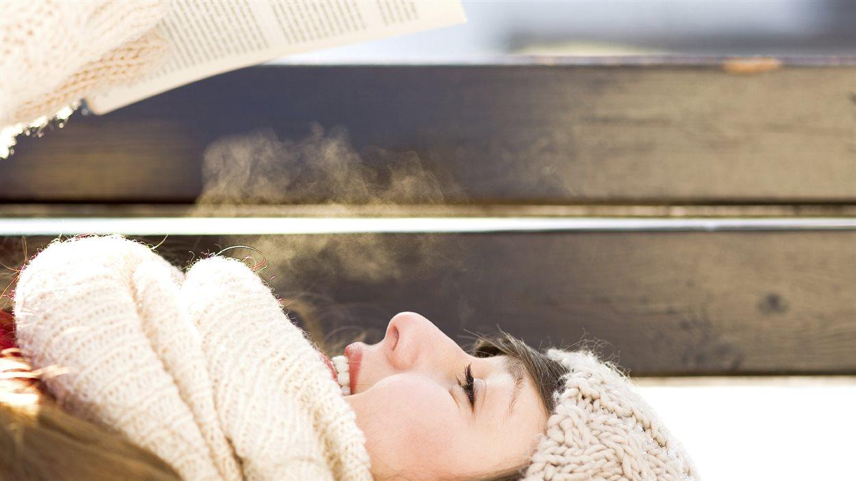 Femme lisant sur un banc en hiver