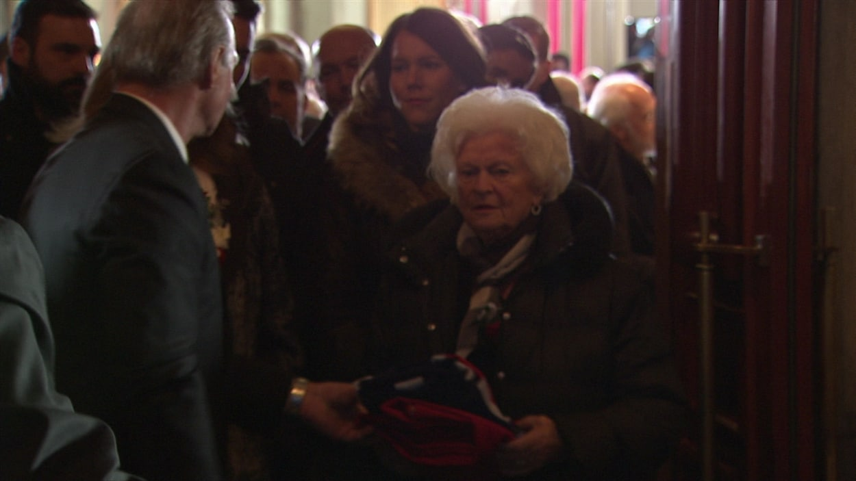 L'épouse de Jean Béliveau reçoit le drapeau du Canadien des mains de Guy Lafleur.