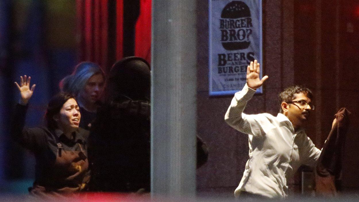 Des otages courent les mains levées en sortant du café Lindt.