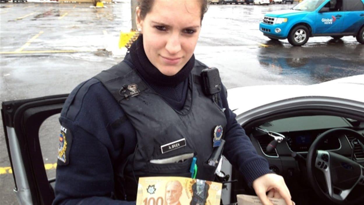 Amélie Brien, policière à Longueuil, distribue des billets de 100 $.