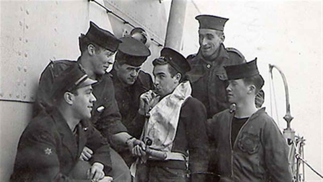 Matelots du HMCS St. Thomas en train de vérifier une ceinture de sauvetage de l'un des rescapés du U-877.