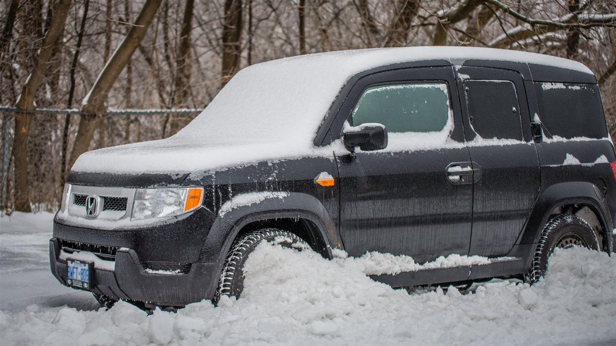 Une voiture prise dans un tas de neige, avec du verglas.