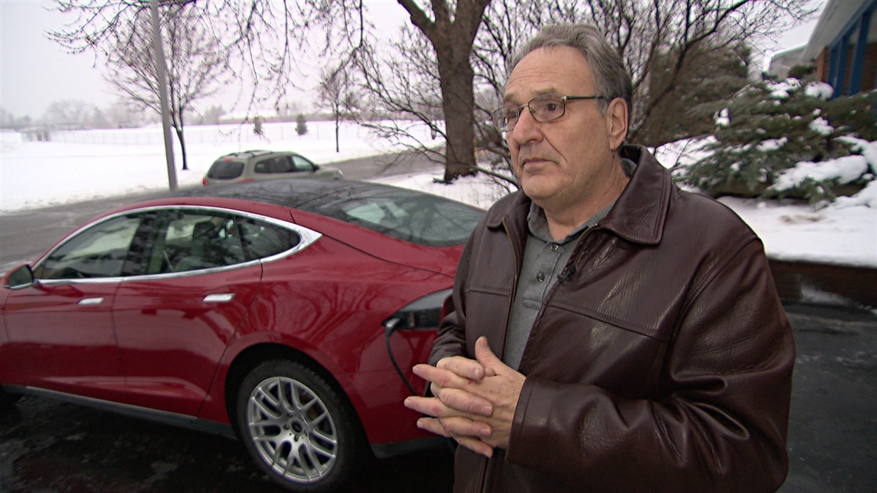 Gérard Gavrel à côté de sa voiture électrique.