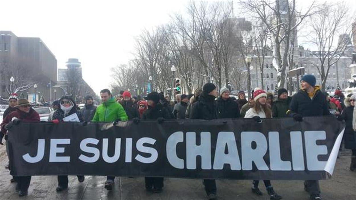 Les marcheurs abordent une banderole en soutien à Charlie Hebdo.