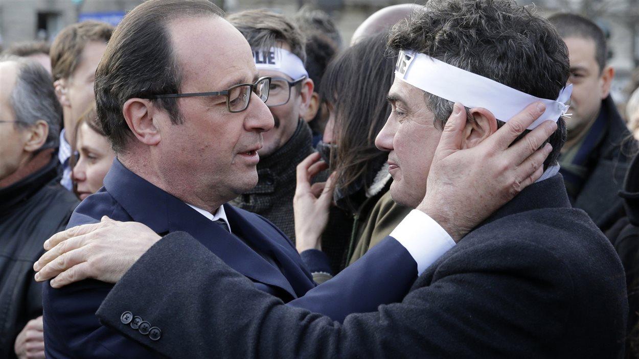 Le président français François Hollande et l'urgentologue et chroniqueur Patrick Pelloux lors de la marche en soutien à Charlie Hebdo, le 11 janvier à Paris.