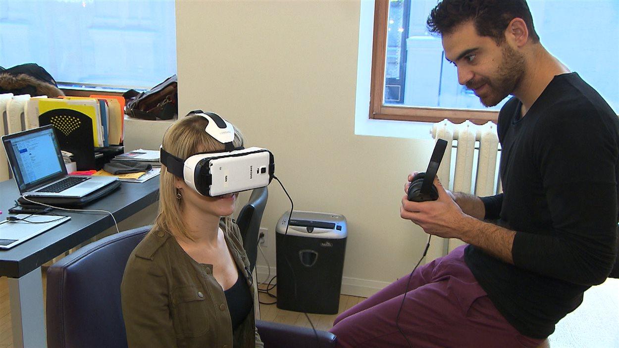 Paul Raphaël explique le fonctionnement du casque de réalité virtuelle à la journaliste Tanya Lapointe