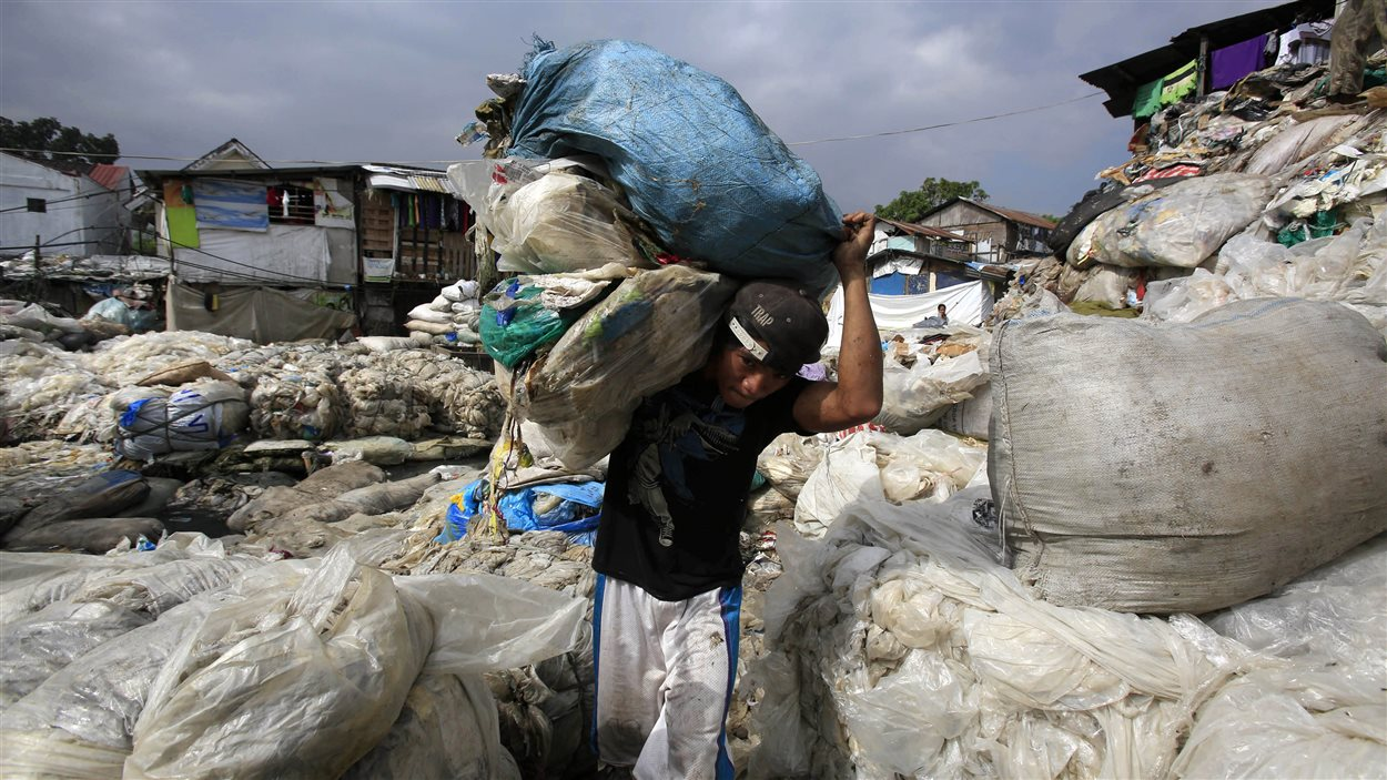Dans un bidonville de Manille, aux Philippines, un homme transporte des déchets pour aller les vendre.