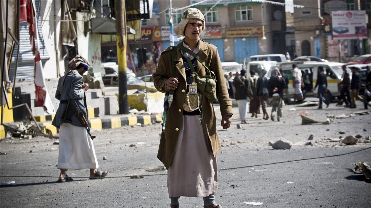 Un milicien chiite monte la garde sur la route qui mène au palais présidentiel, à Sanaa.