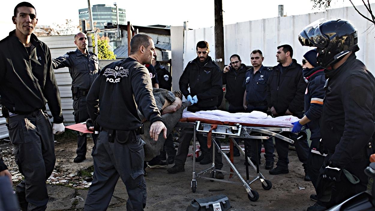 Des policiers préparent une civière pour évacuer des blessés.